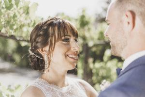 Braut lächelt ihren Bräutigam an.